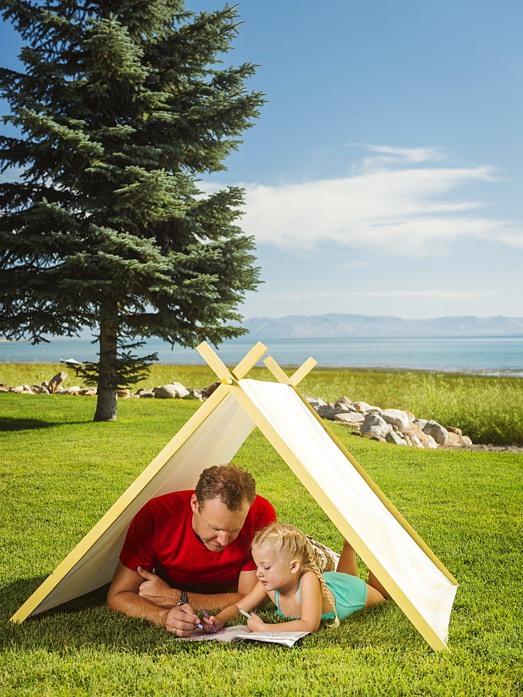 Father and daughter (2-3) playing in tent, Garden City, Utah