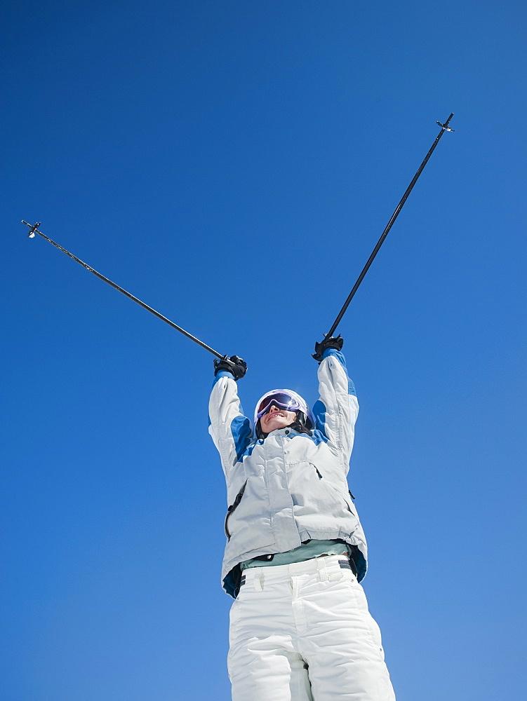 Woman holding ski poles over head