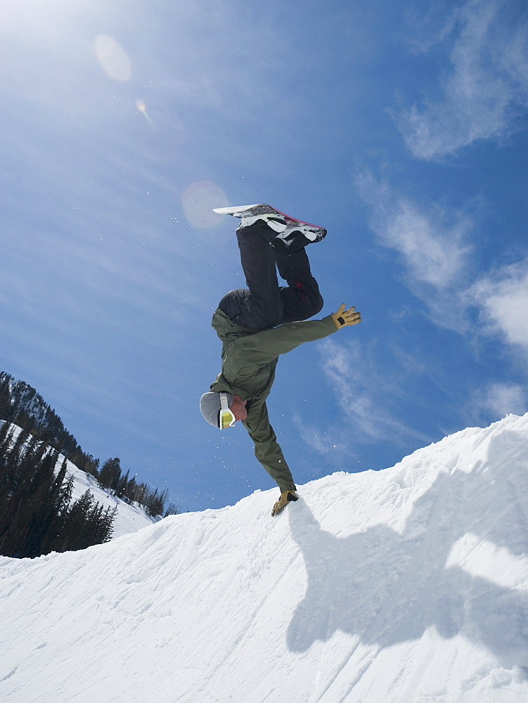 Man performing trick on snowboard