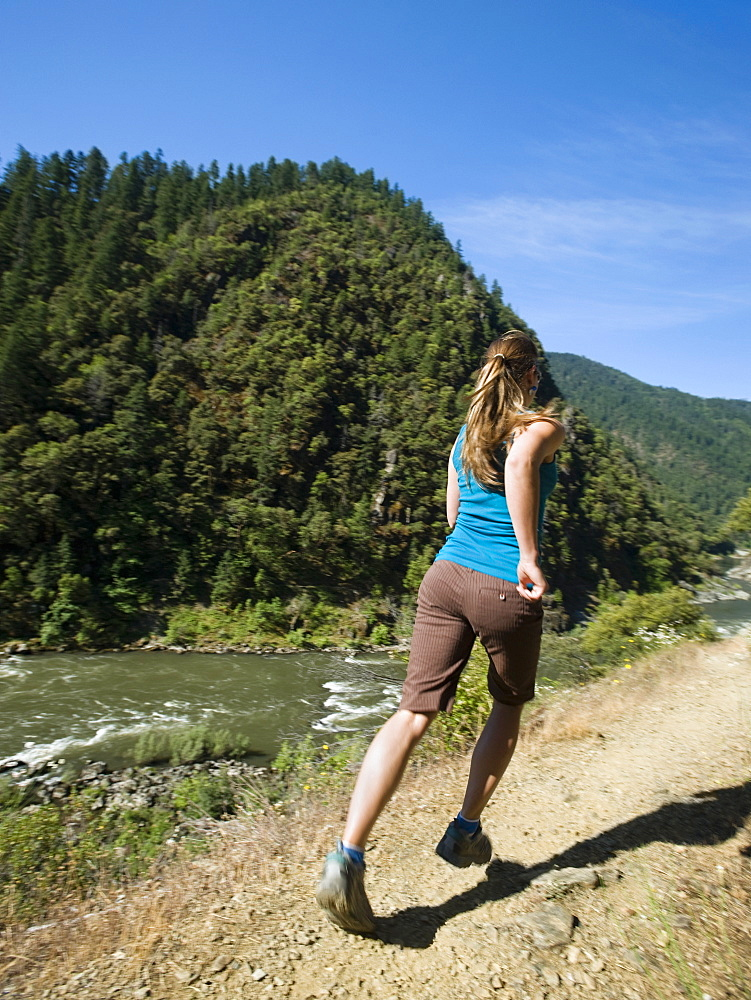 Woman running on riverside trail