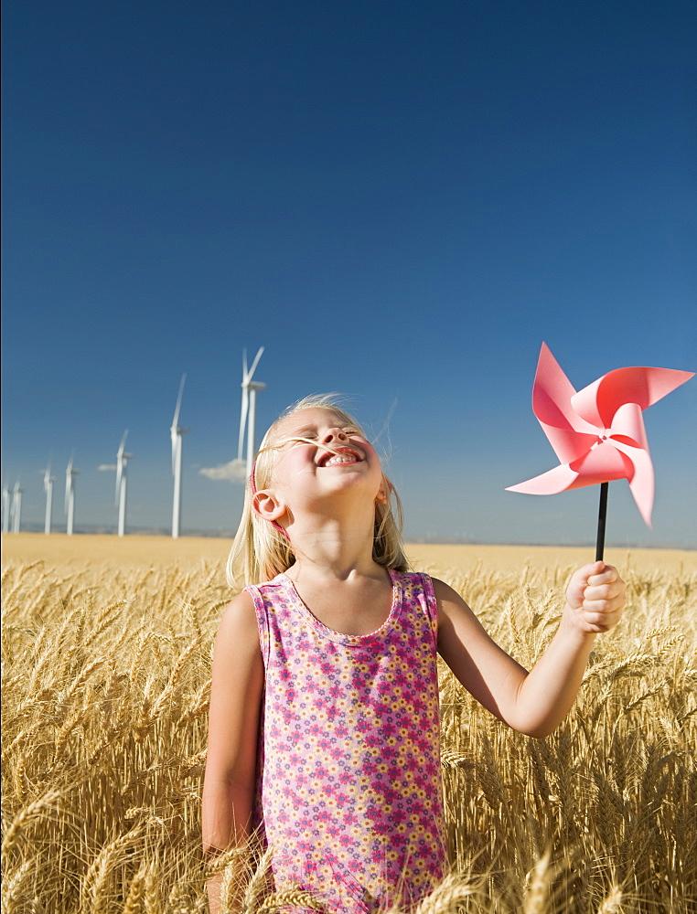 Smiling girl holding pinwheel on wind farm