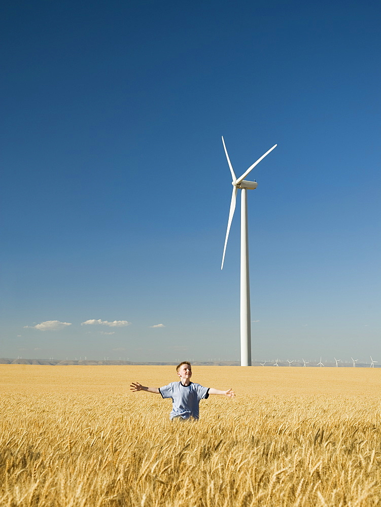 Boy running through field on wind farm