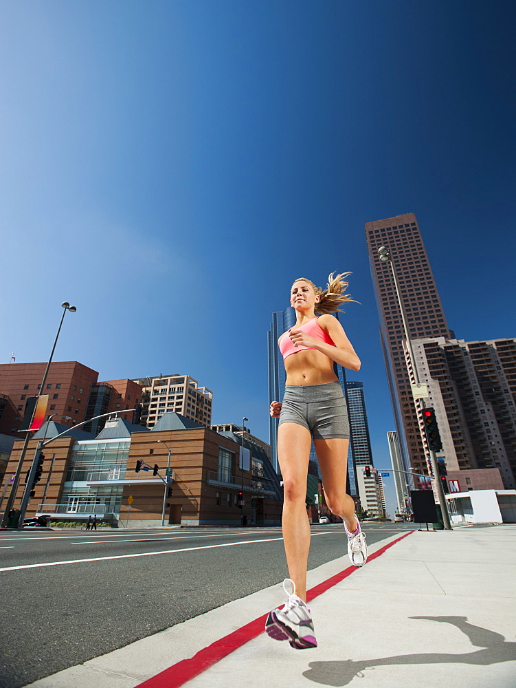 USA, California, Los Angeles, Young woman running on city street, USA, California, Los Angeles