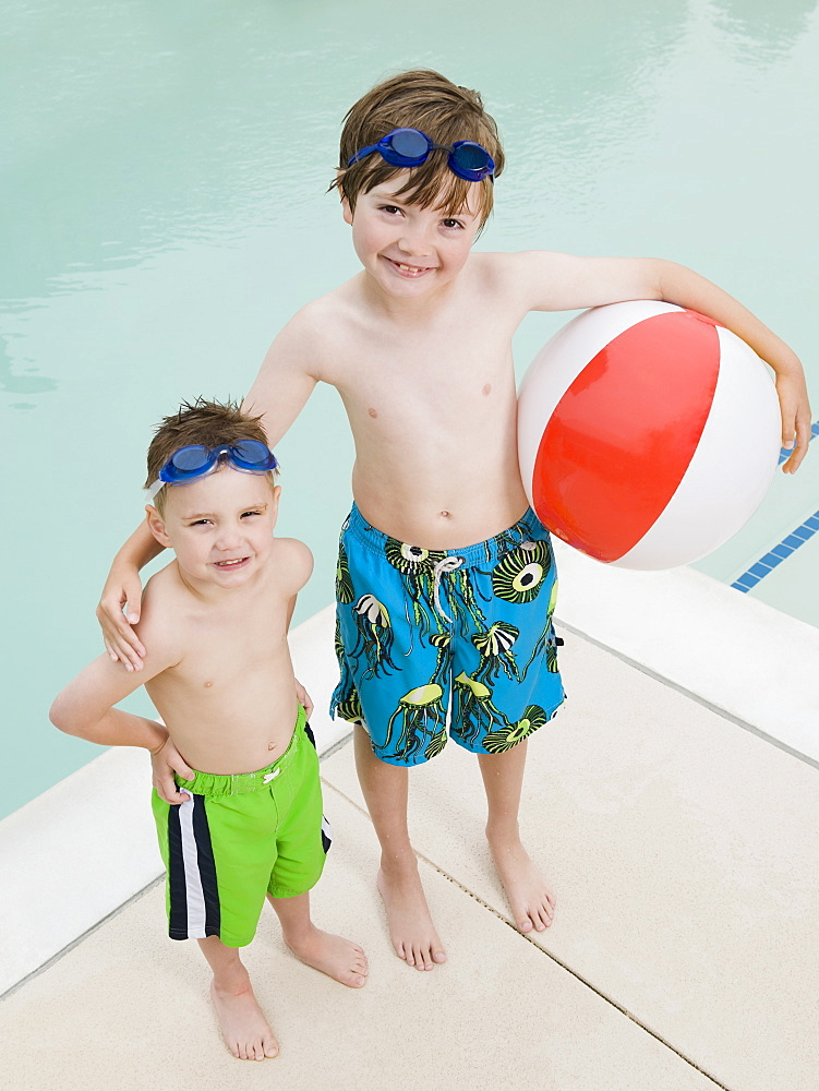 Brothers posing by swimming pool