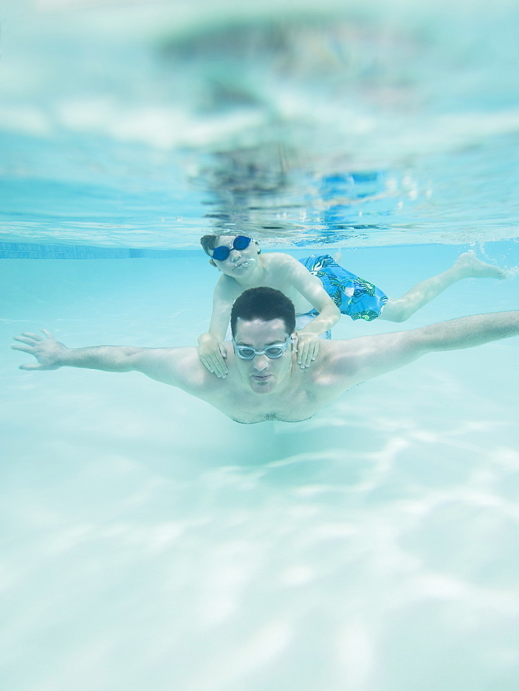 Boy swimming on father's back underwater