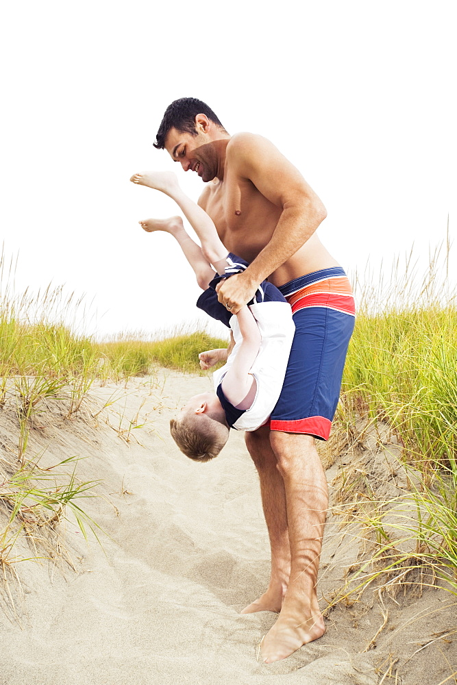 Father holding son upside down on beach