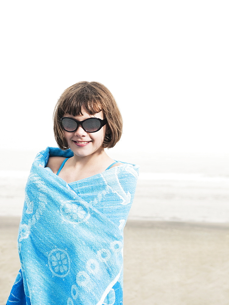 Portrait of girl in sunglasses wrapped in a towel on beach