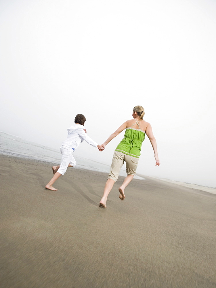 Mother and daughter holding hands and running on beach