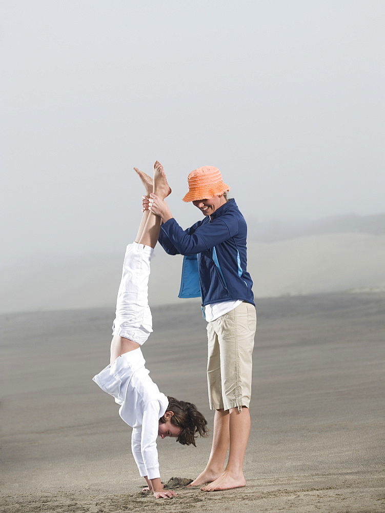 Mother holding daughter upside down on beach