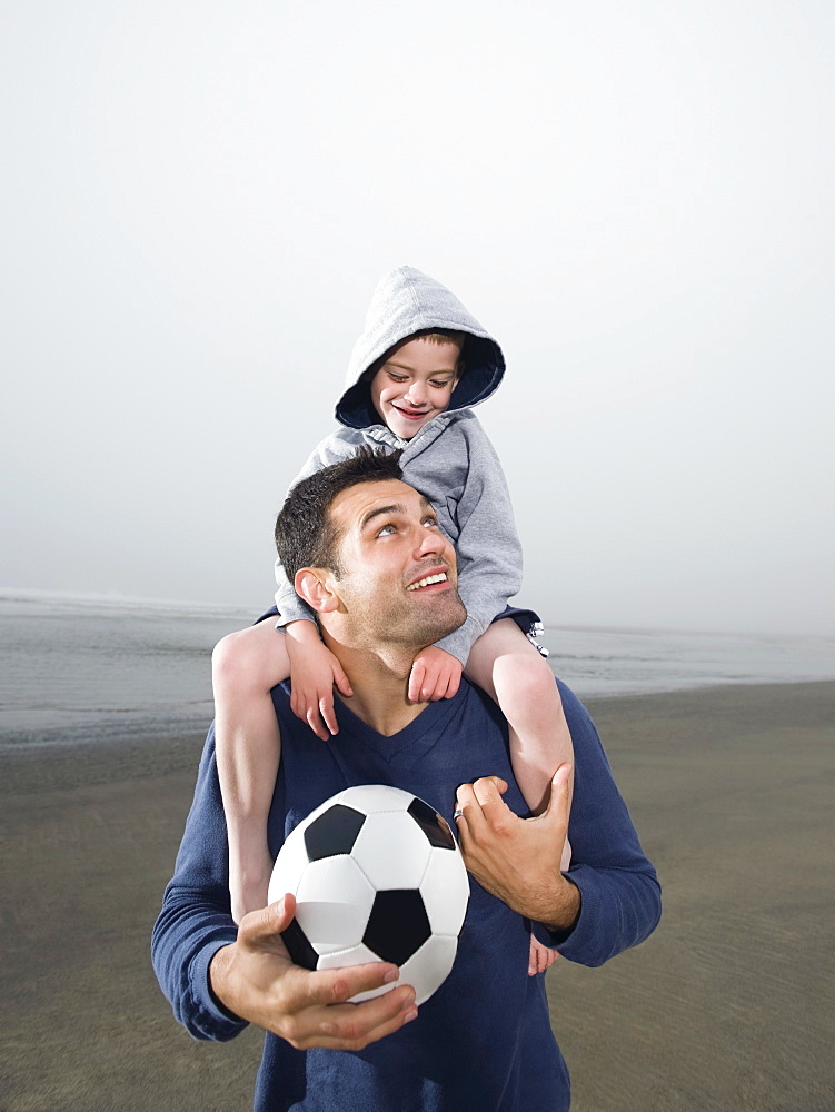 Father carrying son on shoulders and holding soccer ball on beach