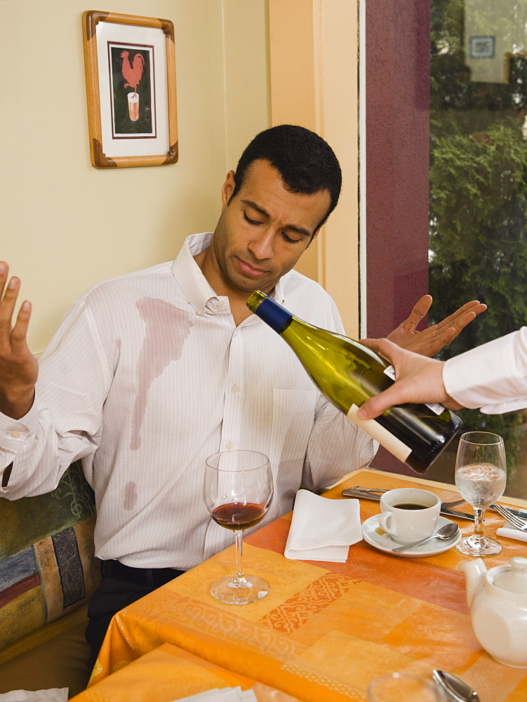 Waiter spilling wine on customer