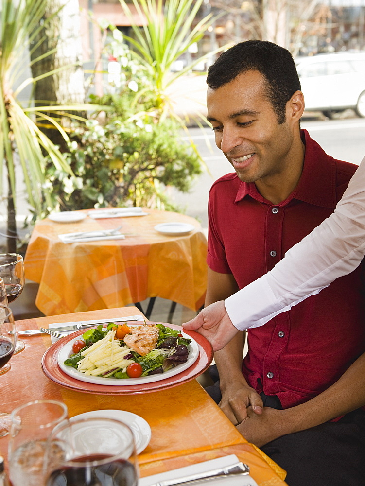 Waiter serving food to man in restaurant
