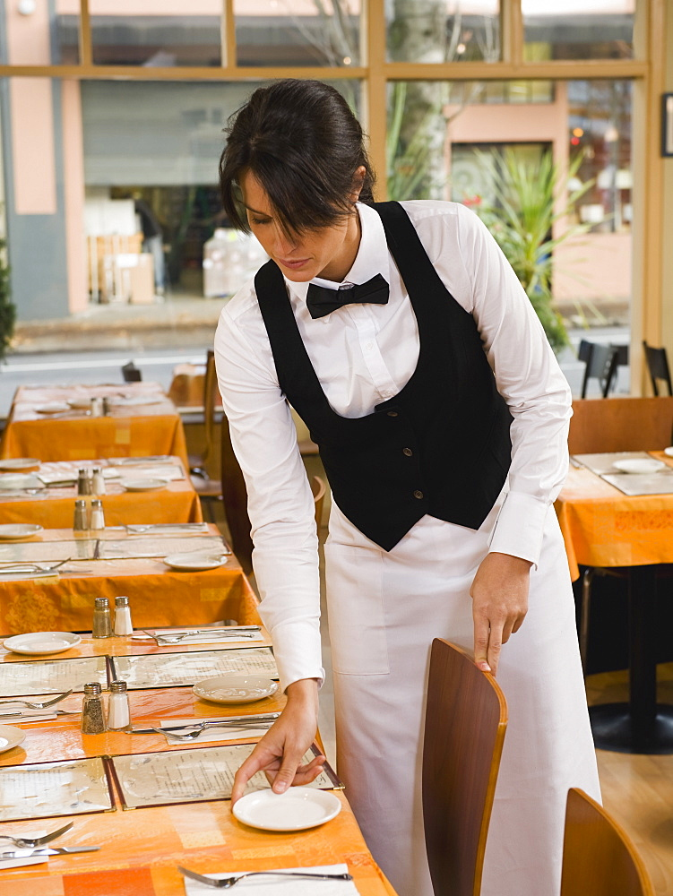 Waitress setting restaurant tables