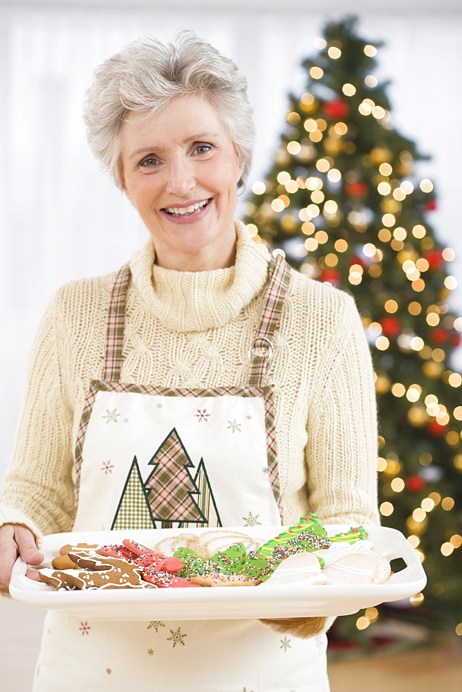 Senior woman holding tray of Christmas cookies