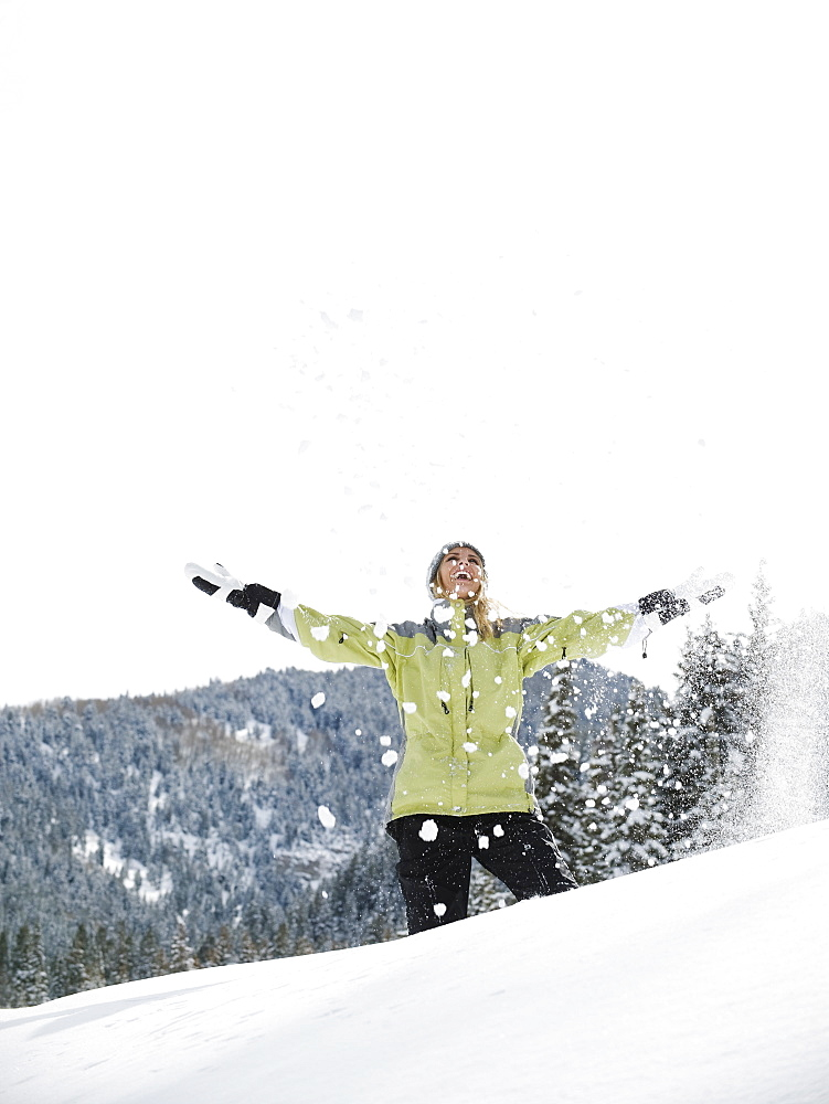 A woman throwing snow up in air