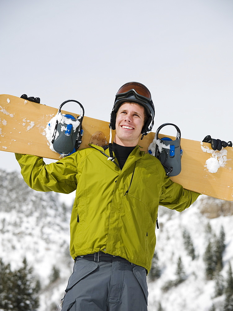 A snowboarder holdiing his snowboard