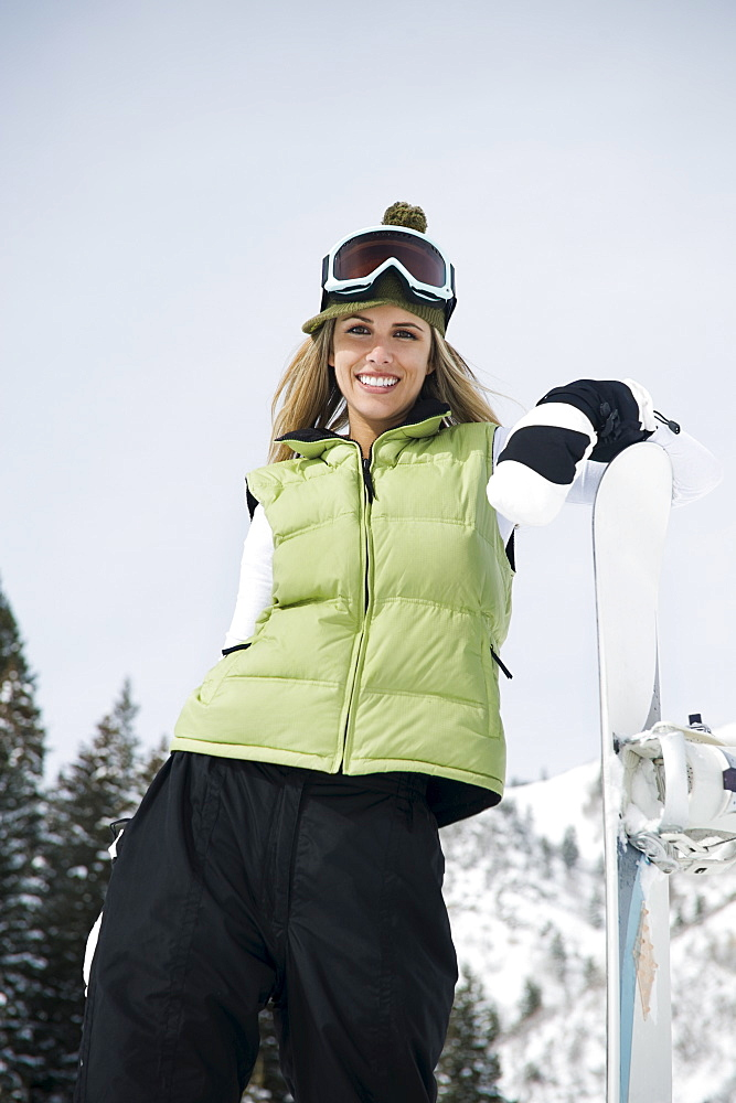 A snowboarder leaning on snowboard