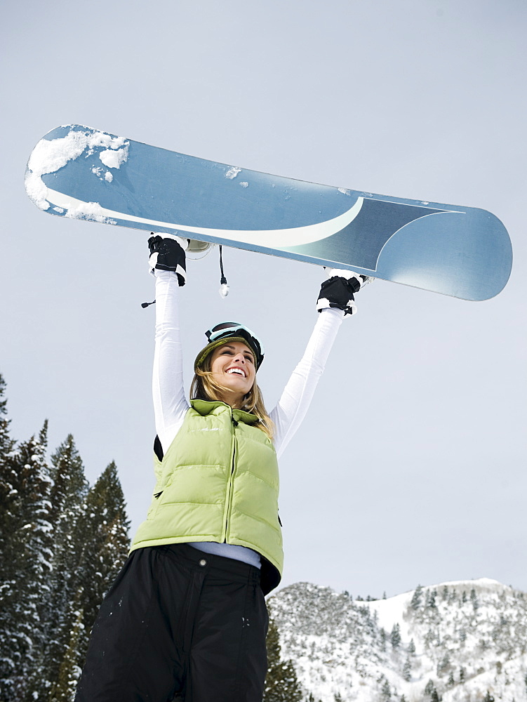 A snowboarder holding up her snowboard