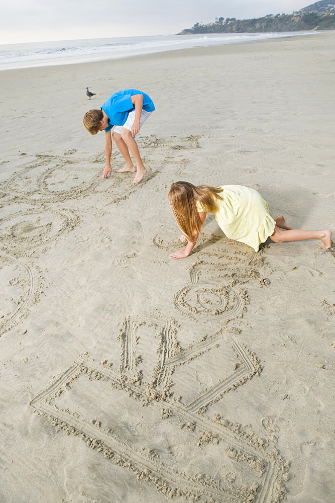 Children writing on beach