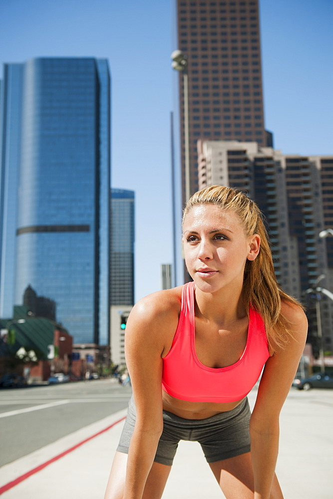 USA, California, Los Angeles, Young woman resting after running on city street, USA, California, Los Angeles