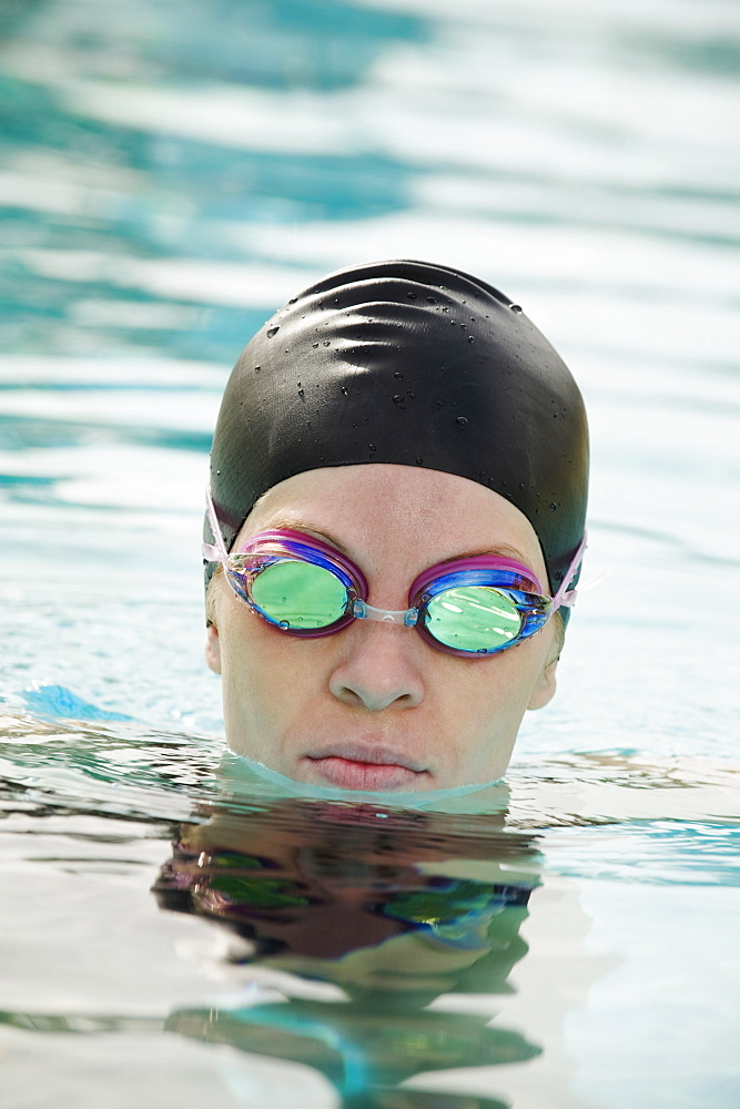 Woman wearing bathing cap and swimming goggles