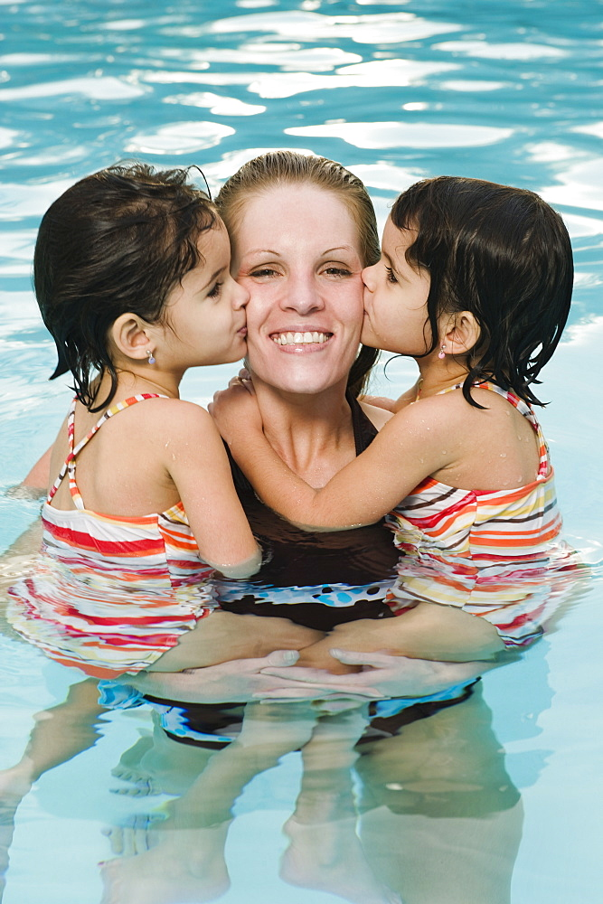 Mother holding daughters in pool