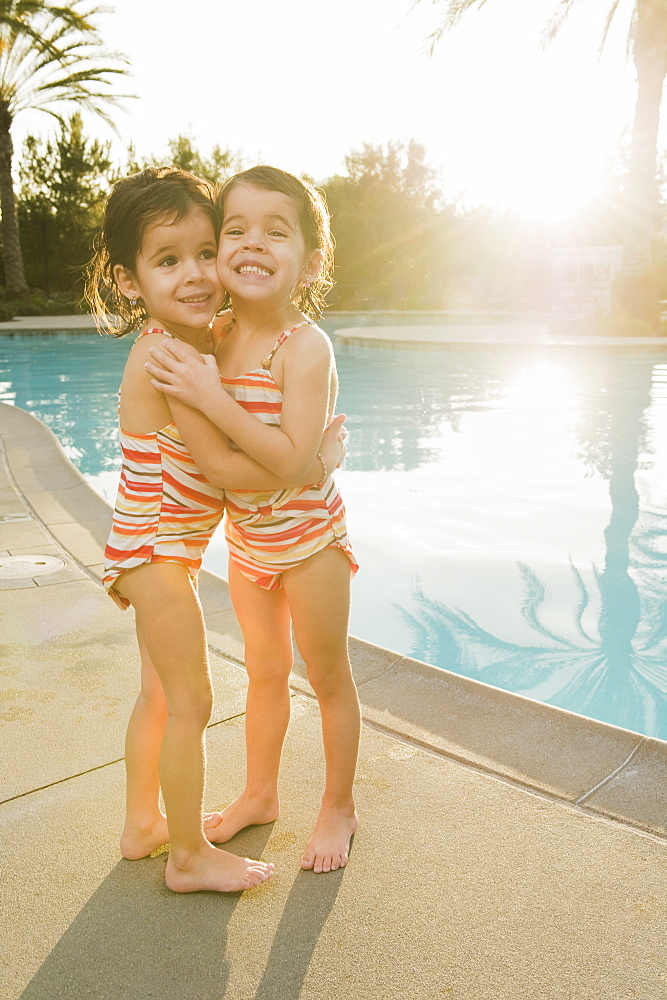Sisters standing beside pool