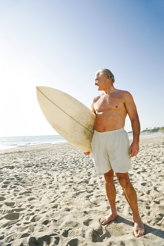 Man holding surfboard on beach