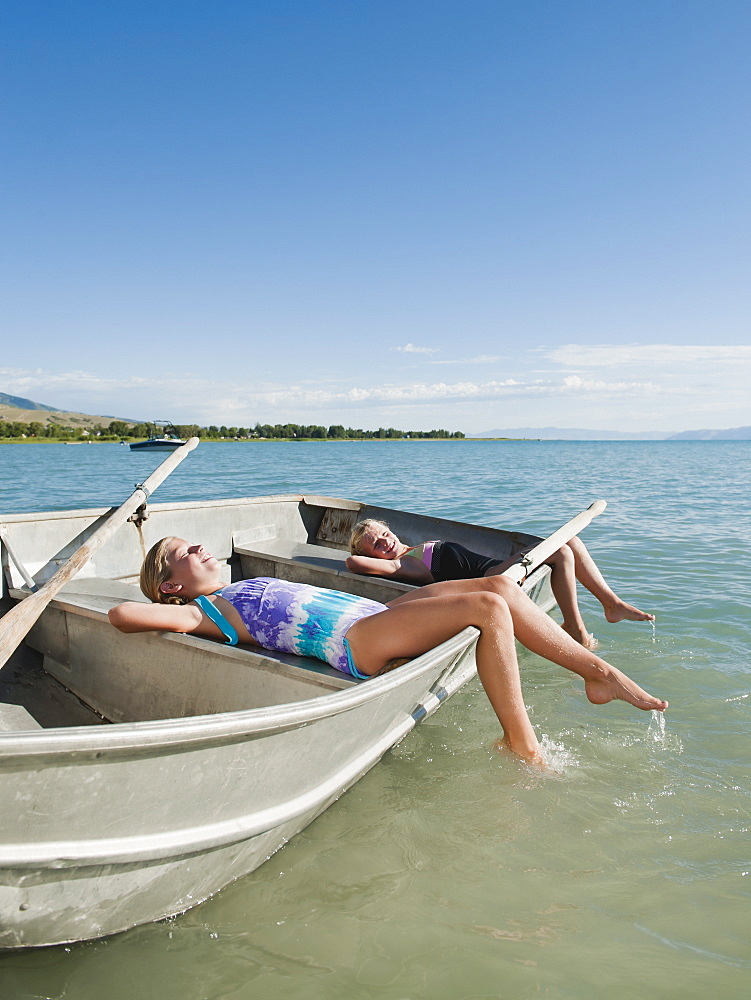Girls (6-7,8-9) resting on boat