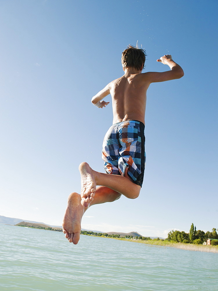 Boy (12-13) jumping into lake