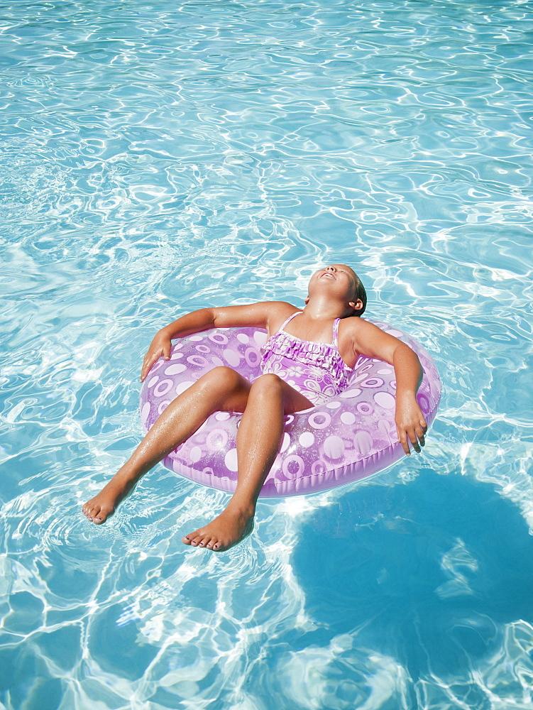 Girl (8-9) floating on rubber ring