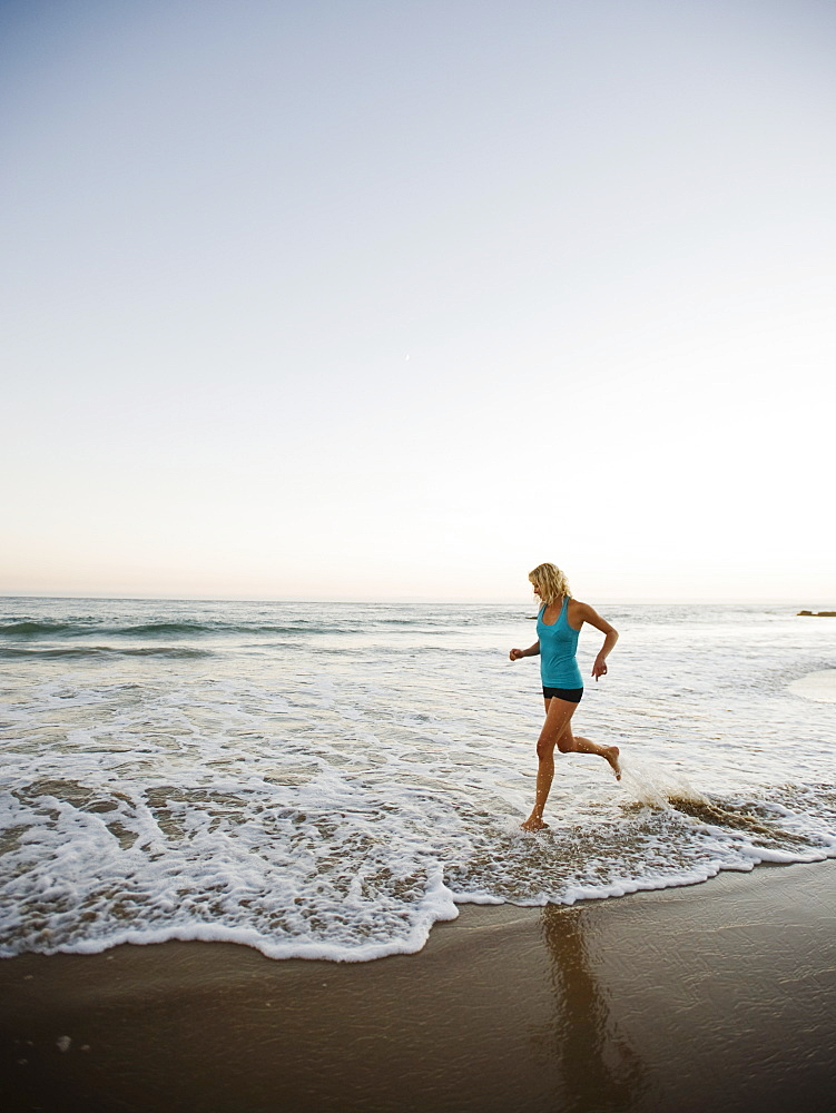Portrait of woman running on beach