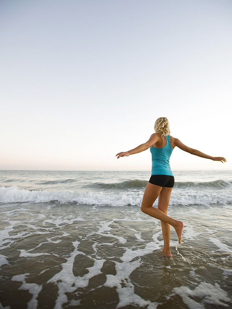 Portrait of woman running on beach