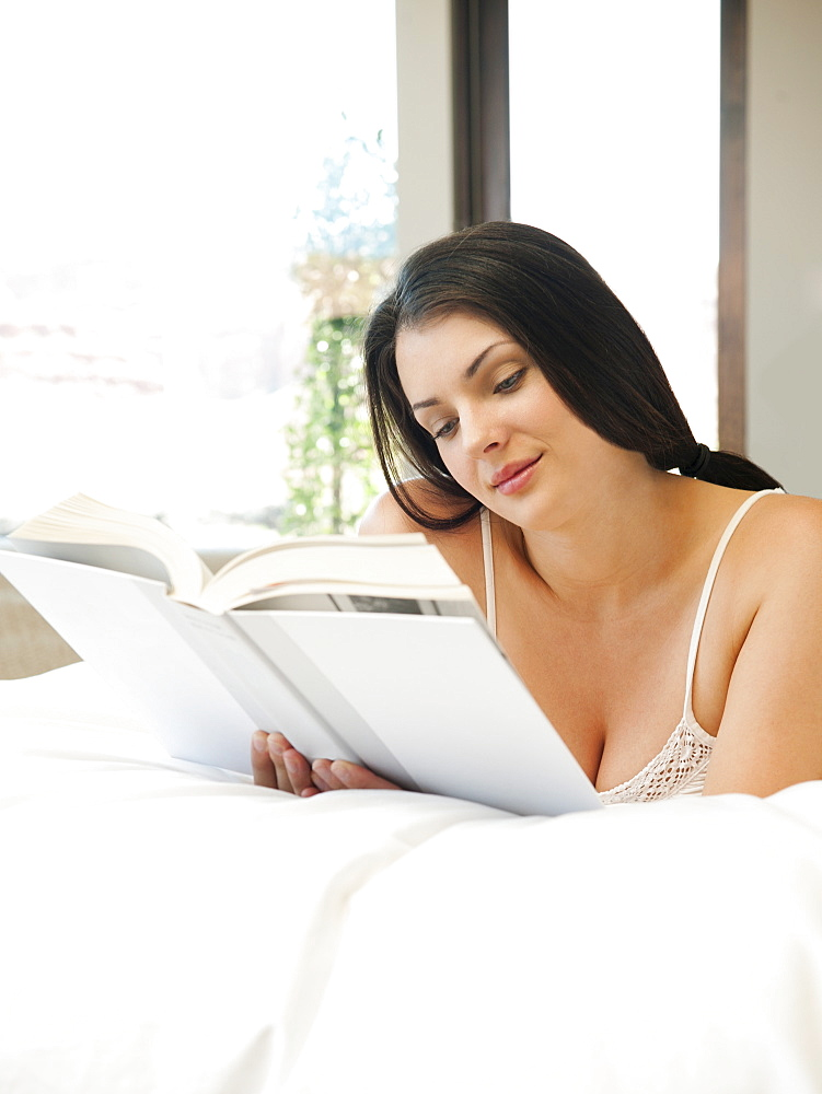Young attractive woman reading book in bed
