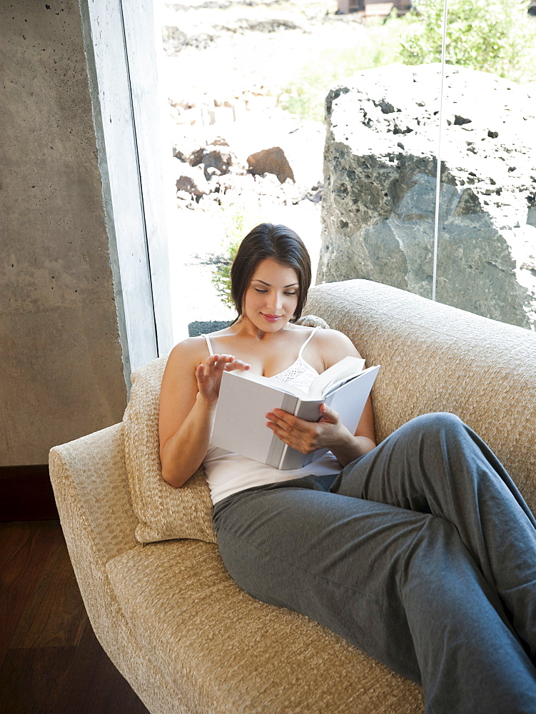Young attractive woman sitting on sofa, reading book