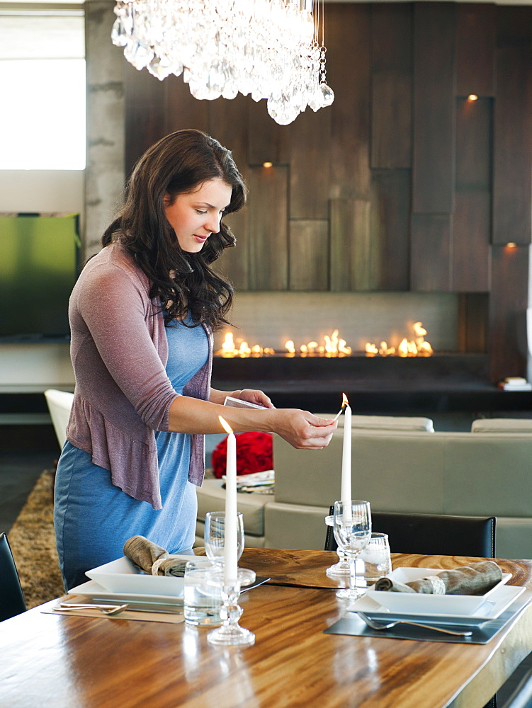 Young attractive woman lighting candles