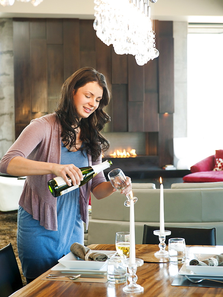 Young attractive woman pouring champagne into glasses