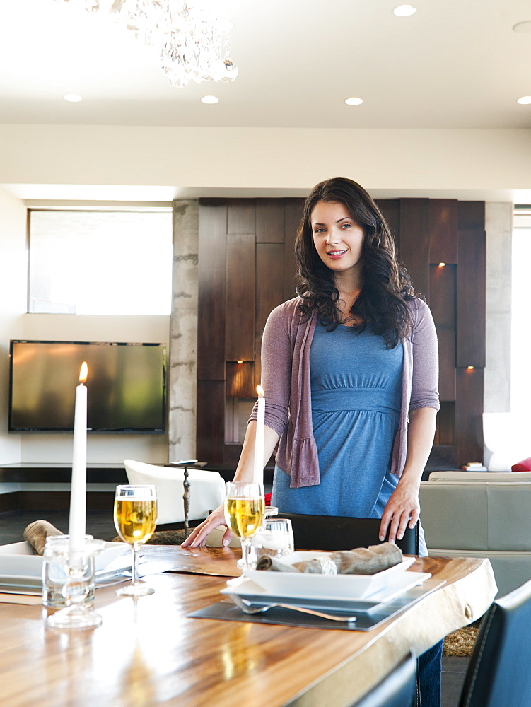 Young attractive woman standing behind table prepared for dinner