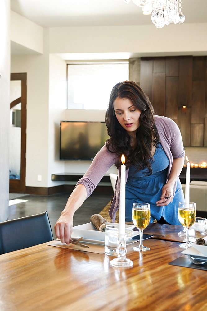 Young attractive woman preparing table for dinner