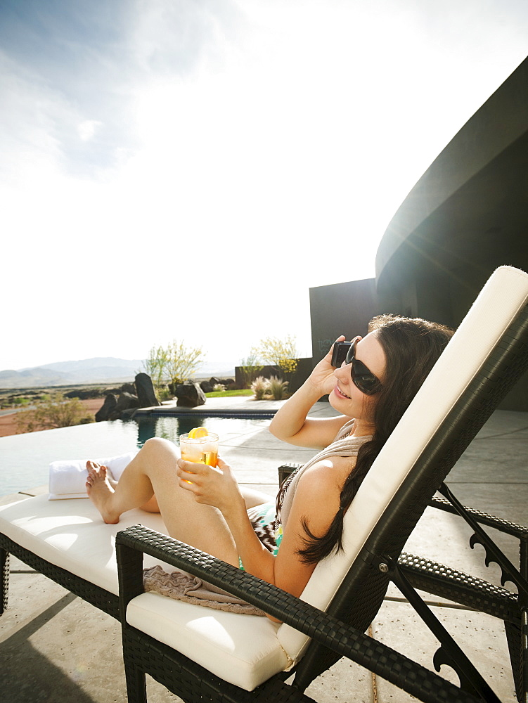 Young attractive woman using mobile phone while sitting by swimming pool, USA, Utah, St. George