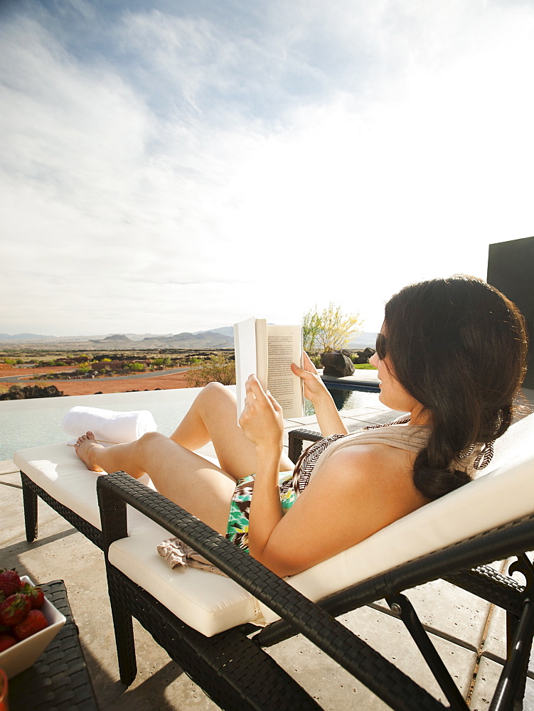 Young attractive woman reading book by swimming pool, USA, Utah, St. George