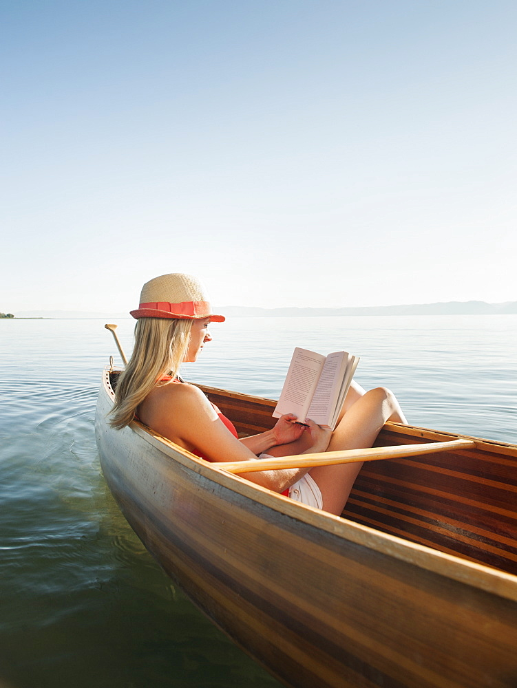 Young woman relaxing in canoe, and reading book