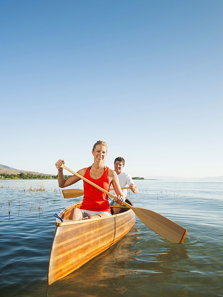 Portrait of two young people paddling canoe
