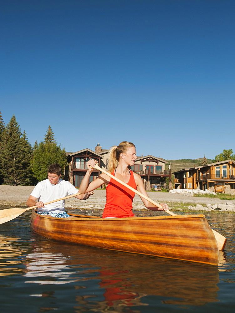 portrait of two young people paddling canoe, USA, Utah, Garden City