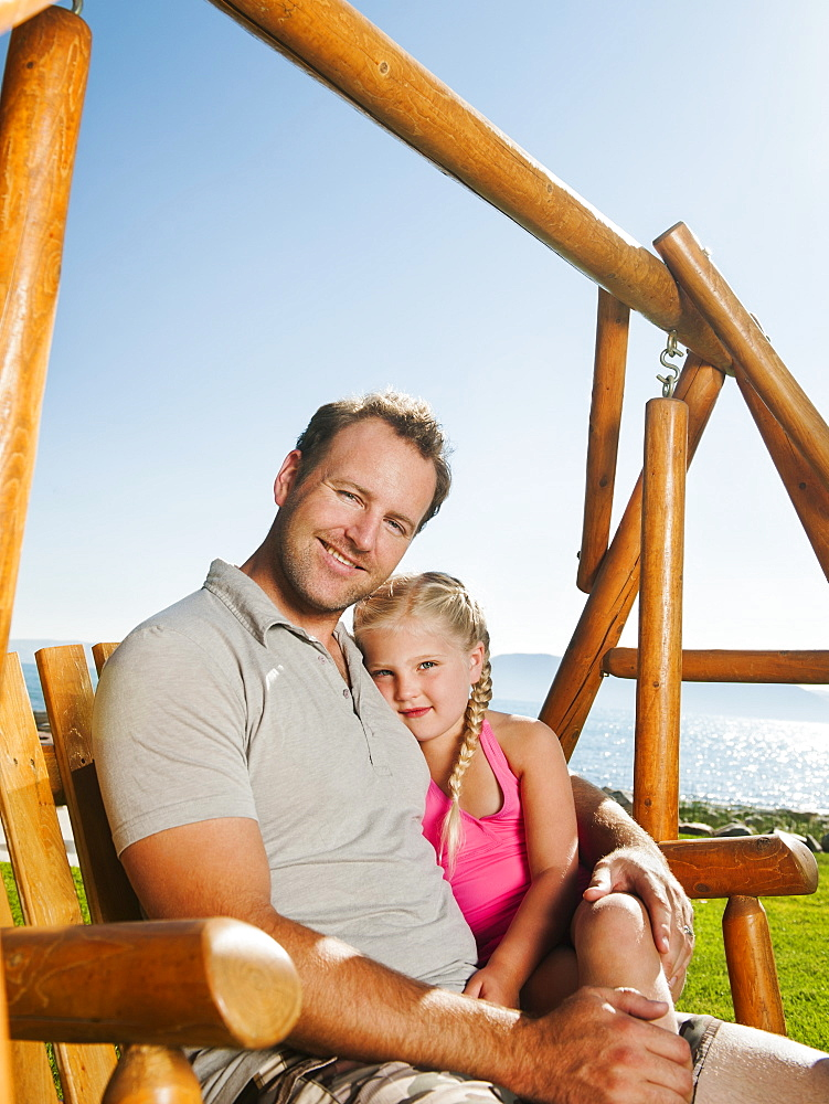 Portrait of father with daughter (4-5) on swing, USA, Utah, Garden City
