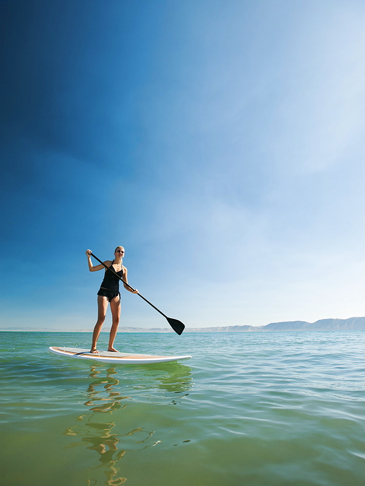 Young woman standing on paddleboard