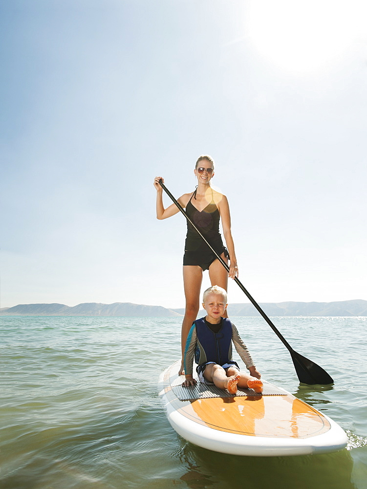 Portrait of young woman with daughter (4-5) on paddleboard