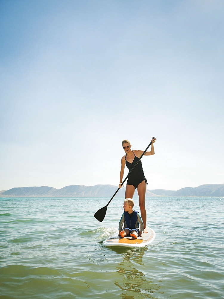 Young woman with daughter (4-5) on paddleboard