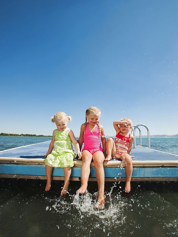 Girls (2-3, 4-5) sitting at the edge of raft and splashing water