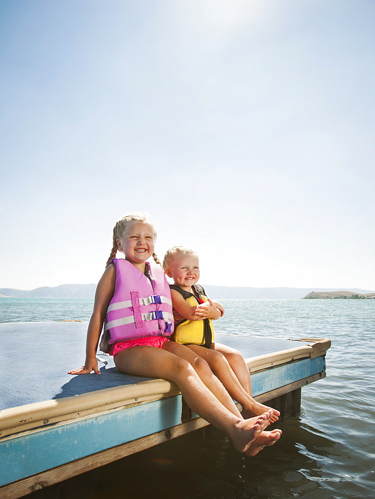 Girls (2-3, 4-5) sitting at the edge of raft in life jackets